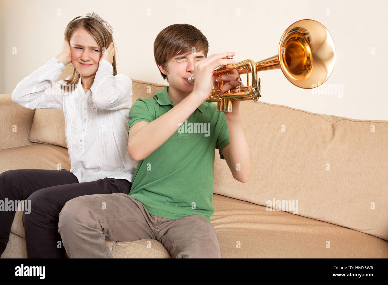 Photo of a brother playing his trumpet too loudly, or badly, and annoying his sister. Stock Photo
