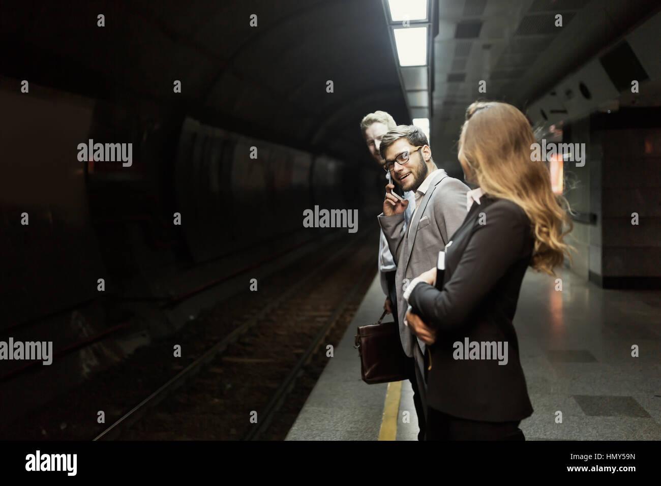 Business people waiting for transportation underground - Stock Image