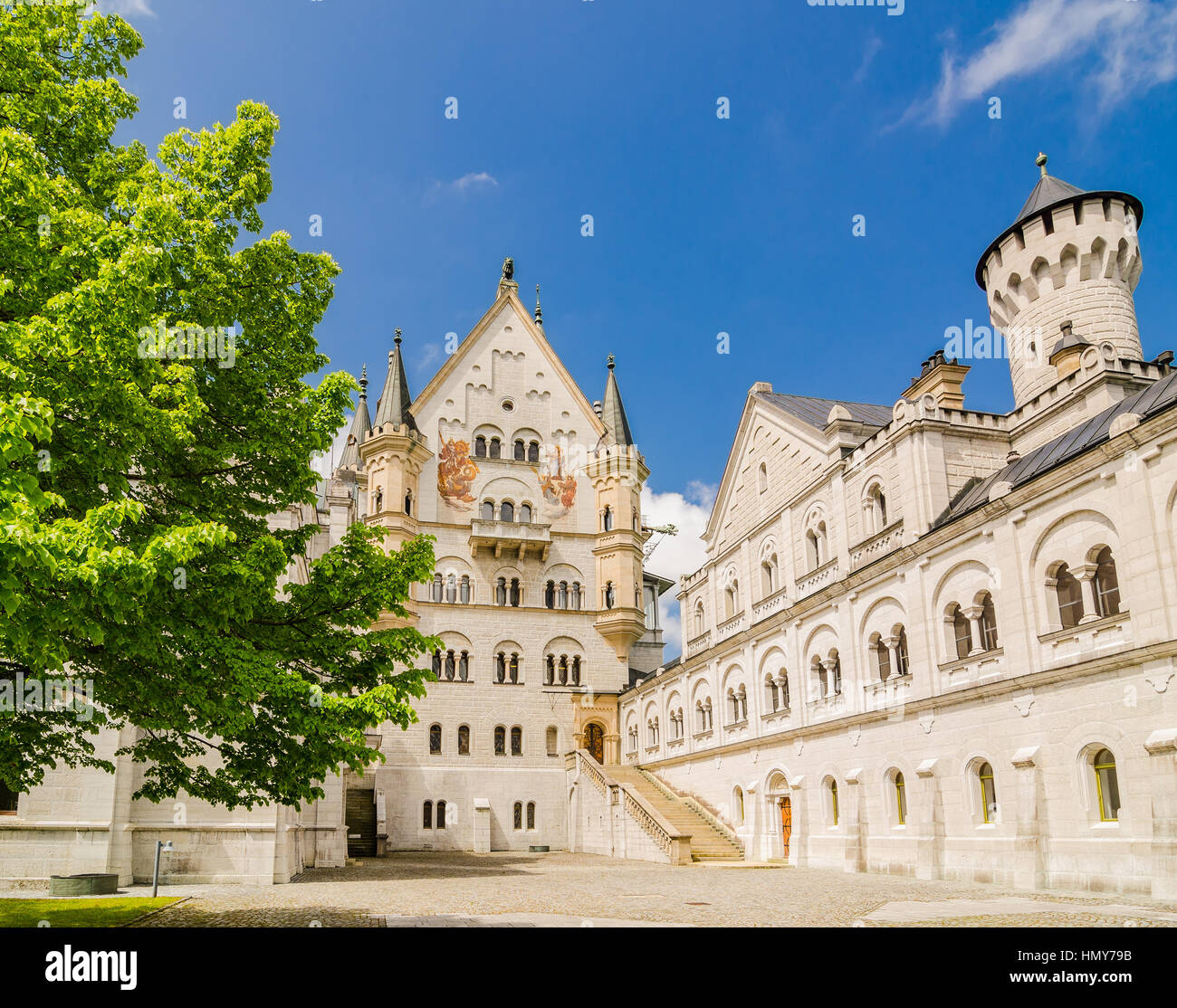 Neuschwanstein Castle is a nineteenth-century Romanesque Revival palace on a rugged hill above the village of Hohenschwangau - Stock Image