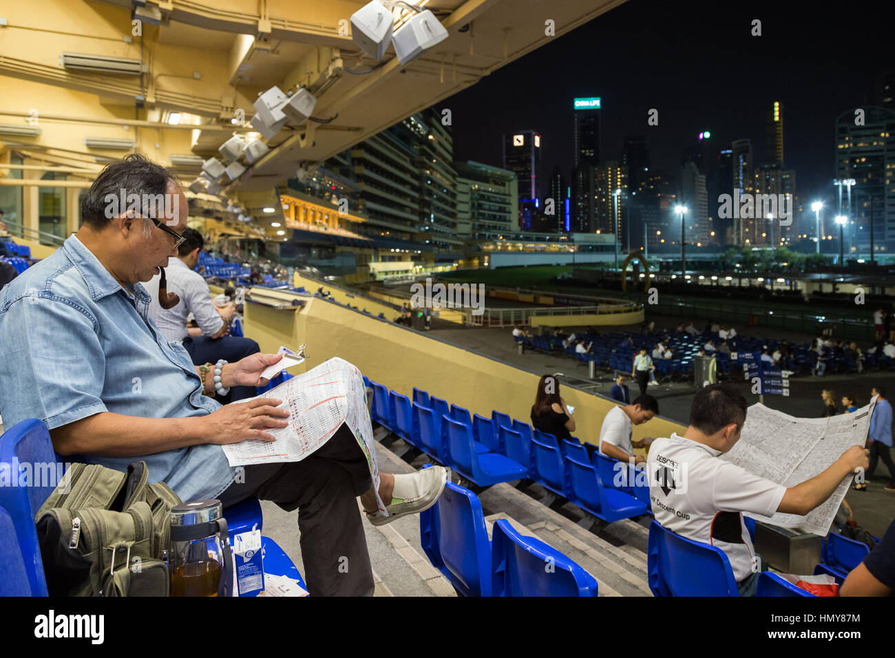 Chinese gambler smoking tobacco pipe and reading newspaper and other people at the Happy Valley Racecourse in Hong - Stock Image