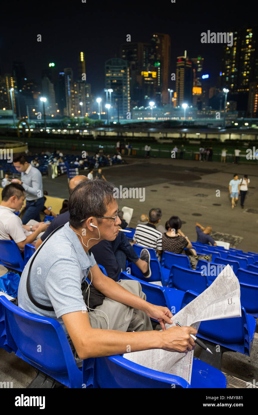 Chinese gambler smoking cigarette and reading newspaper and other people at the Happy Valley Racecourse in Hong - Stock Image