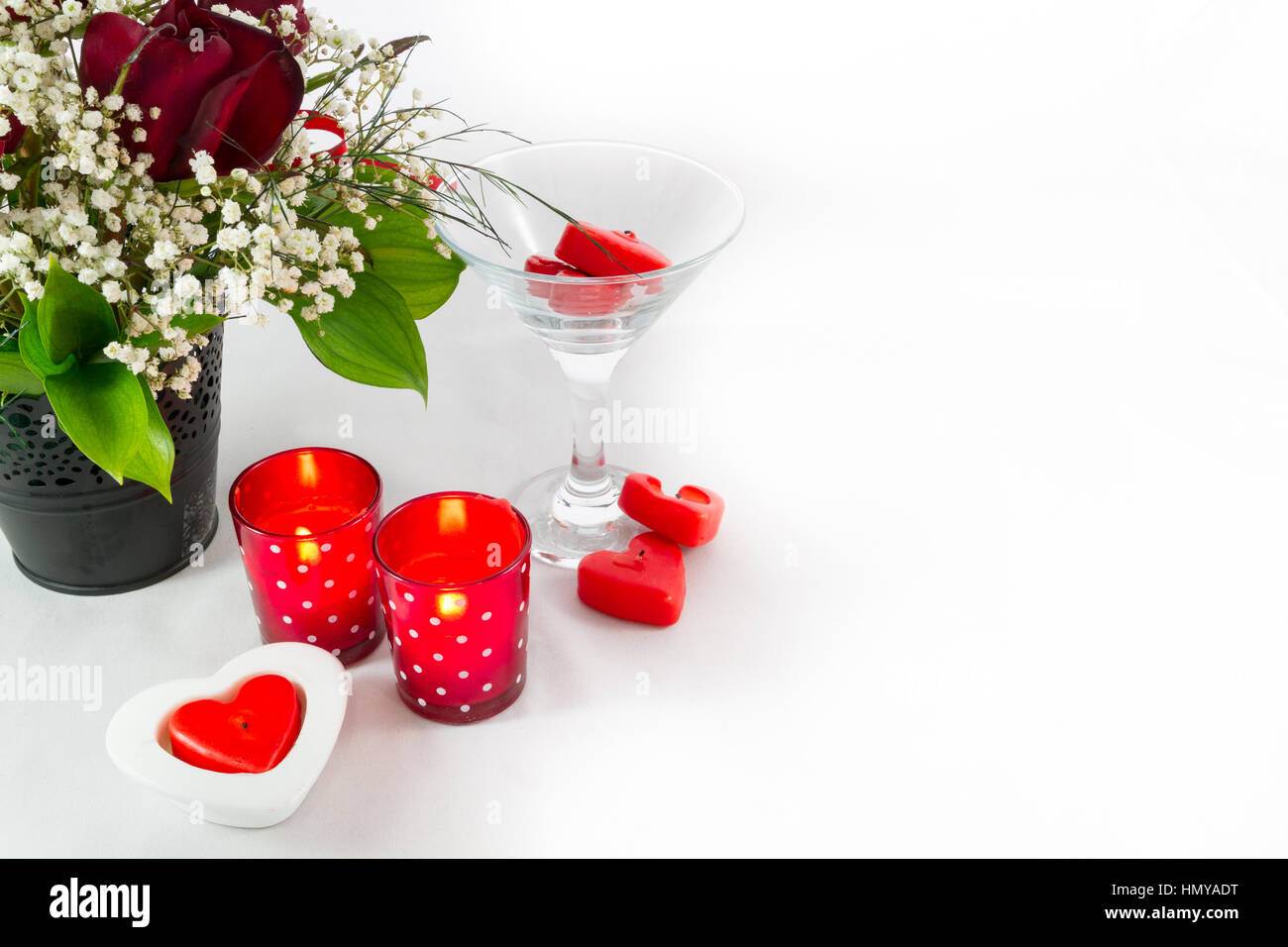 Composition of a Valentines Day Rose Bouquet and Heart shaped Candles on a white background with right copy space - Stock Image