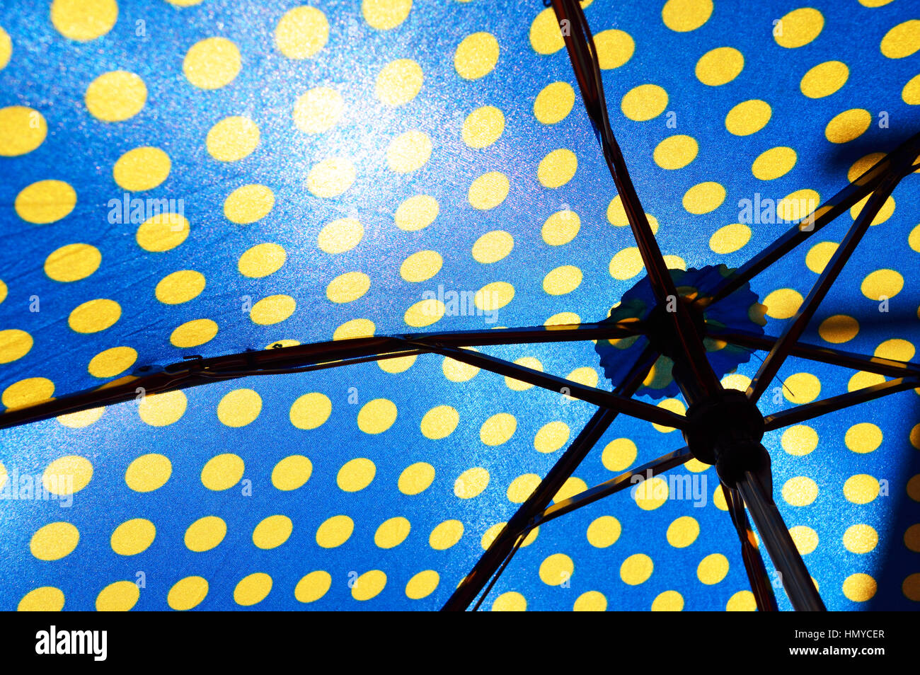 Underside of a blue and yellow umbrella - Stock Image