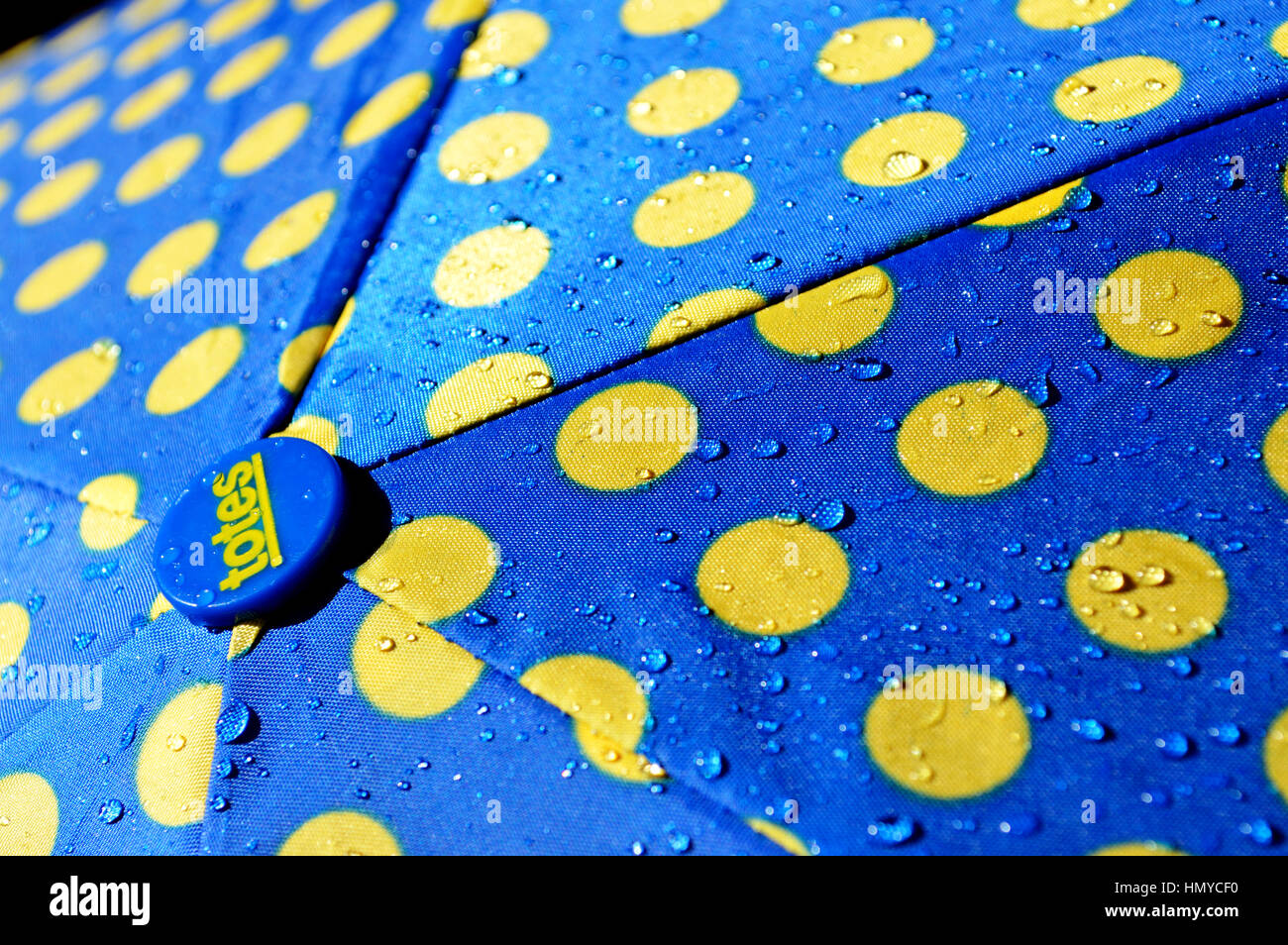 Rain drops on a blue and yellow umbrella. - Stock Image
