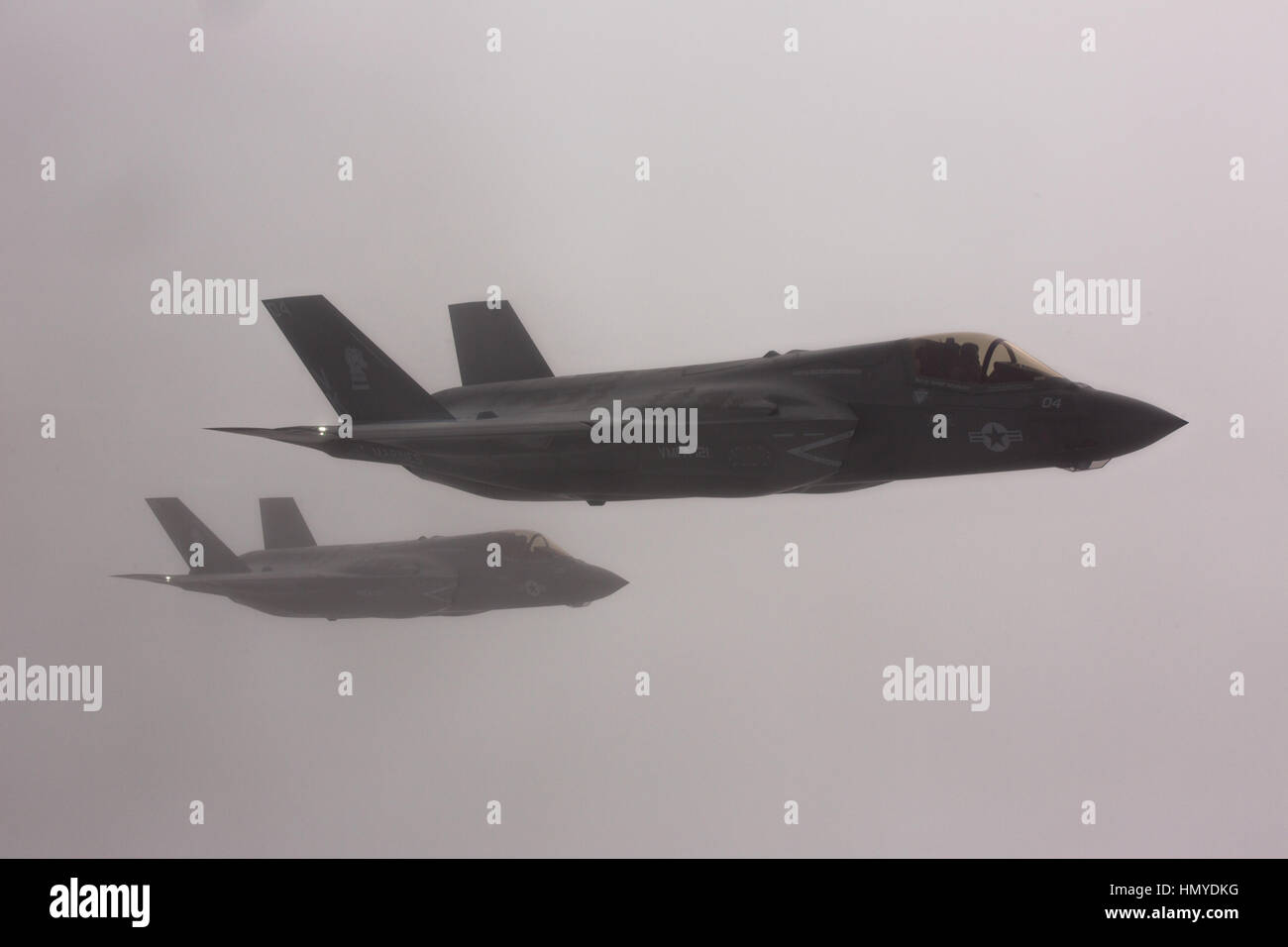 Two Lockheed Martin F-35B Lightning II stealth fighter aircraft fly in formation through a cloud bank on the way - Stock Image