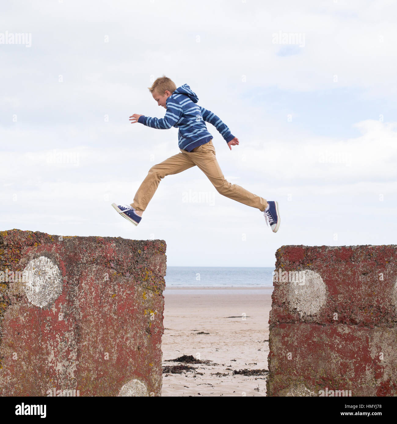 Energetic teenage boy jumping from one rock to another with the beach in the background. - Stock Image