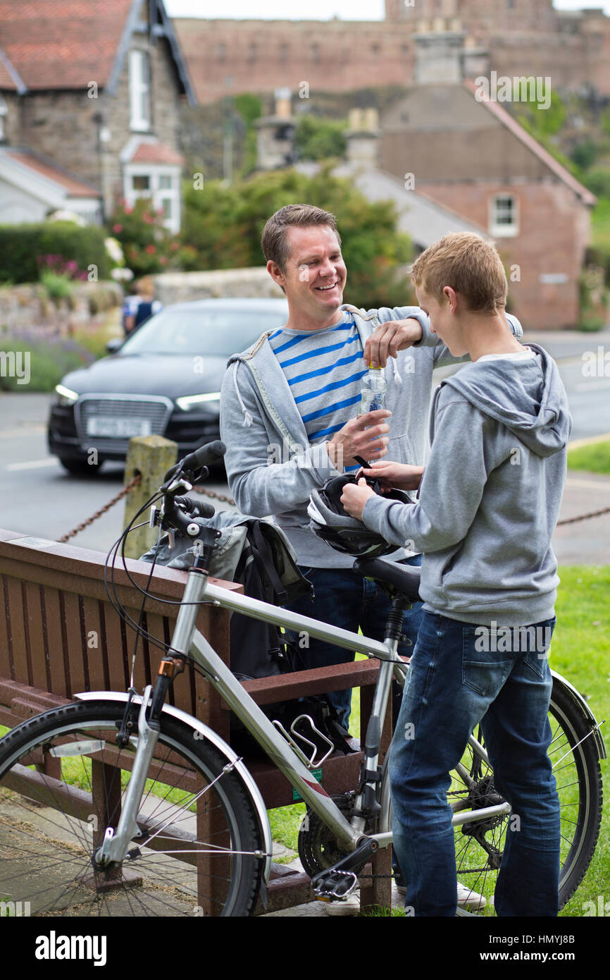 Father and Son stopping in a village in the middle of their bike ride to take a drink. They are wearing casual clothing - Stock Image