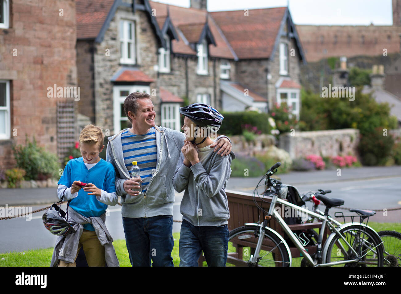 Father and Sons stopping in a village in the middle of their bike ride to take a drink. They are wearing casual - Stock Image