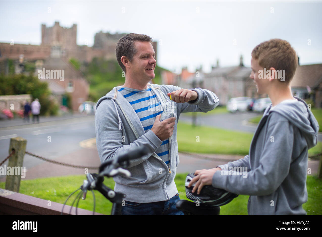 Father and Son stopping in a village in the middle of their bike ride. The father is opening his water while the - Stock Image
