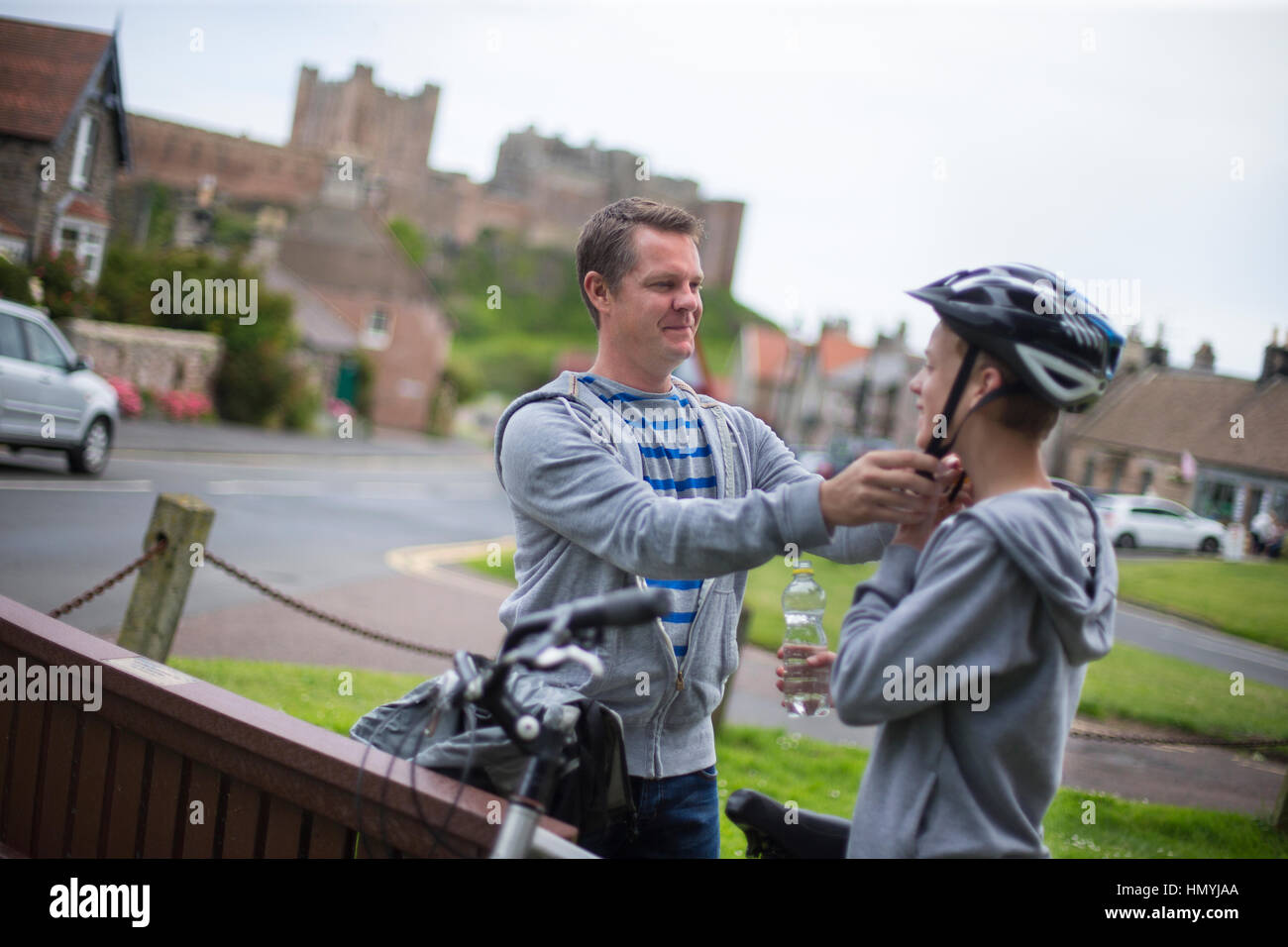 Father putting his helmet on for his son. They are wearing casual clothing and a background of a village and castle - Stock Image