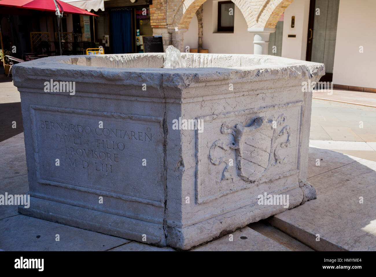 Old well with coat of arms of Marano Lagunare Stock Photo