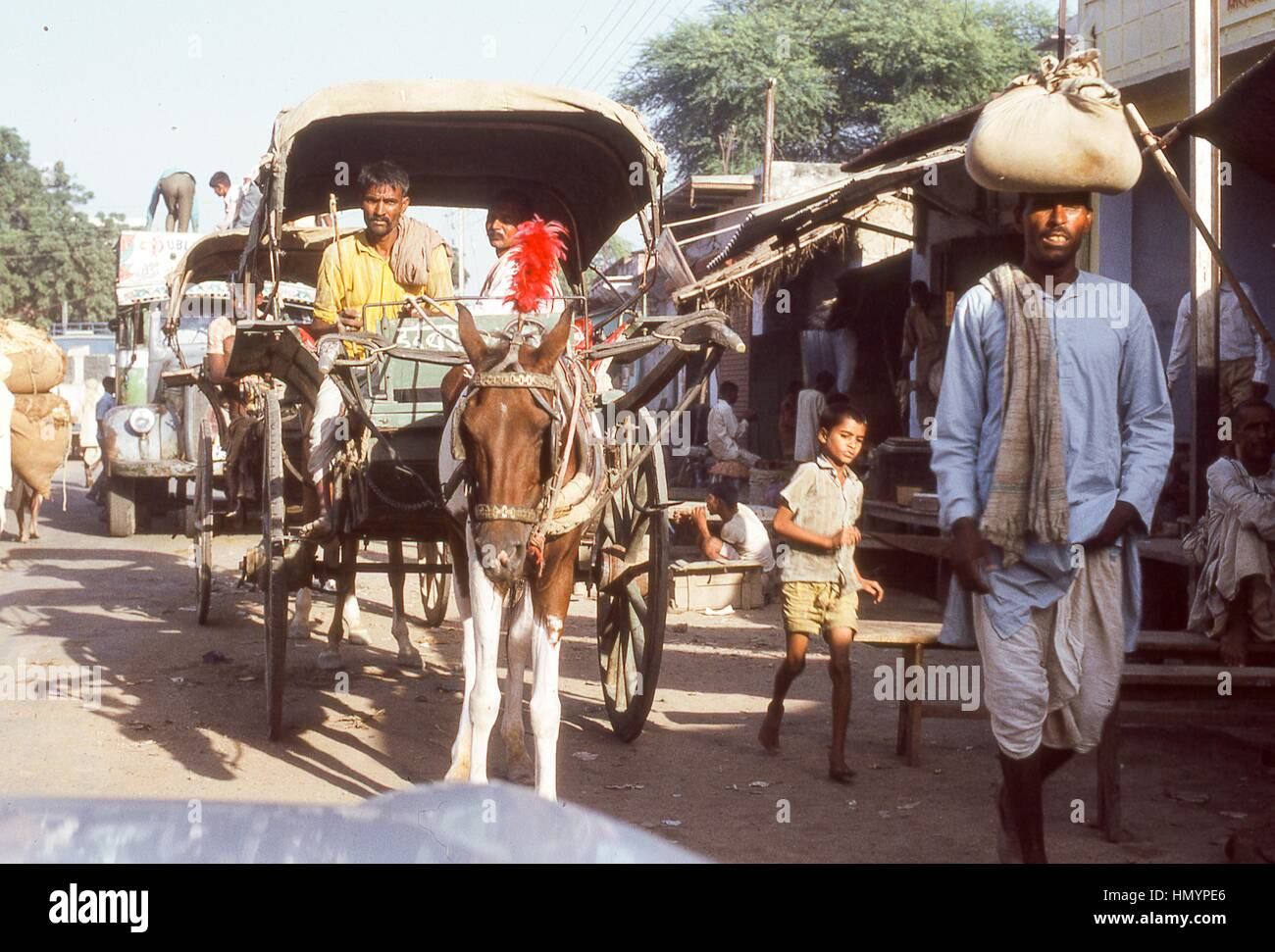 Scene of Indian men and boys leading horse-drawn carriages in the street outside the shop stalls of the Sadar Bazaar - Stock Image