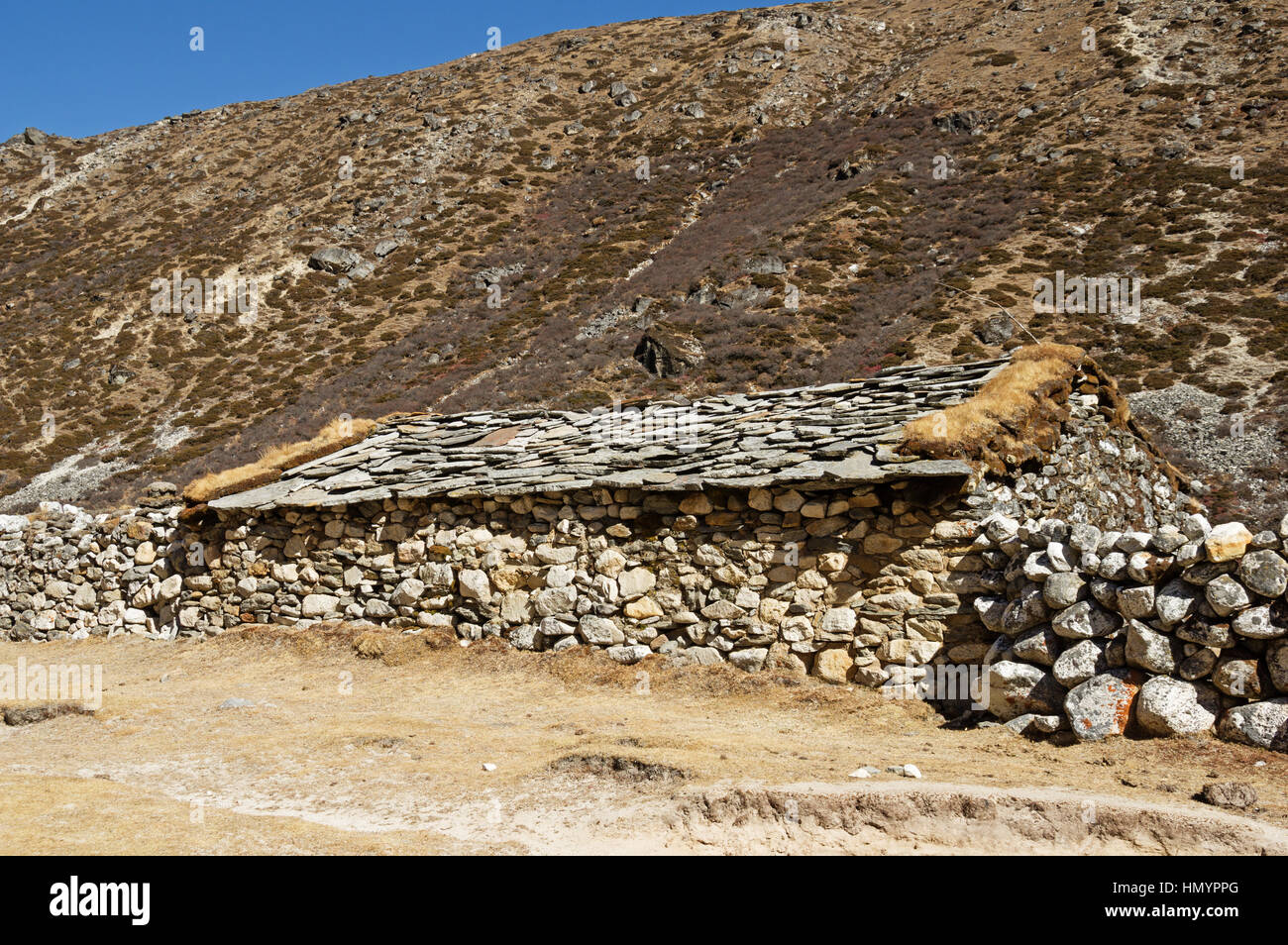 traditional old stone house in the Himalayan region of Nepal with stone roof - Stock Image