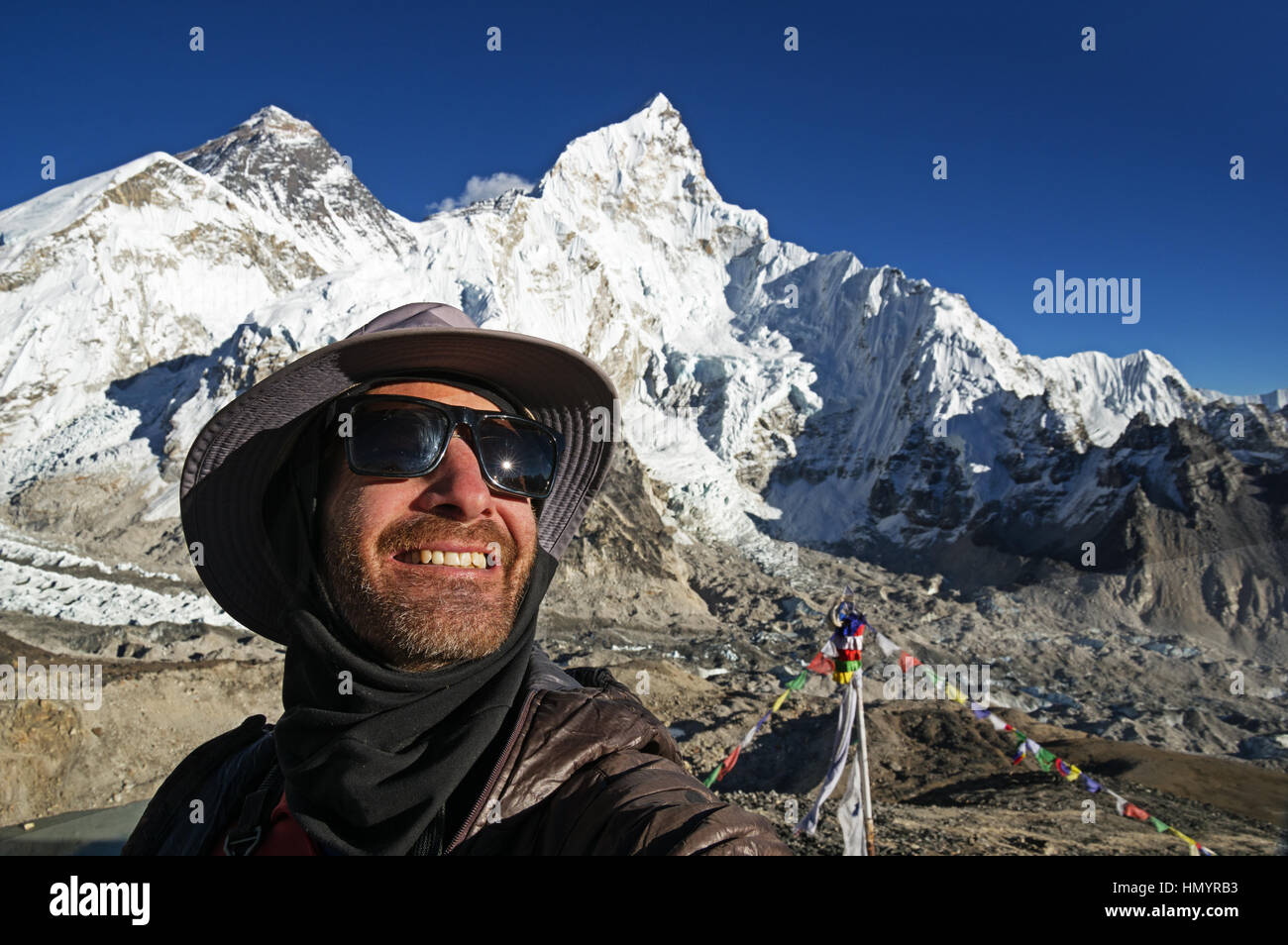 man in a selfie with Mount Everest in the background taken from the summit of Kala Patthar - Stock Image