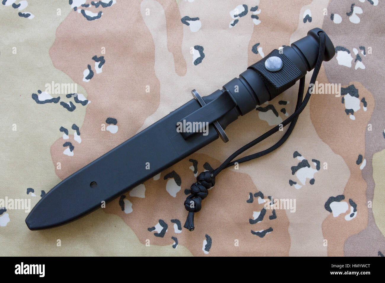 Tactical knife in a case on the sand camouflage. Knife for the military. - Stock Image
