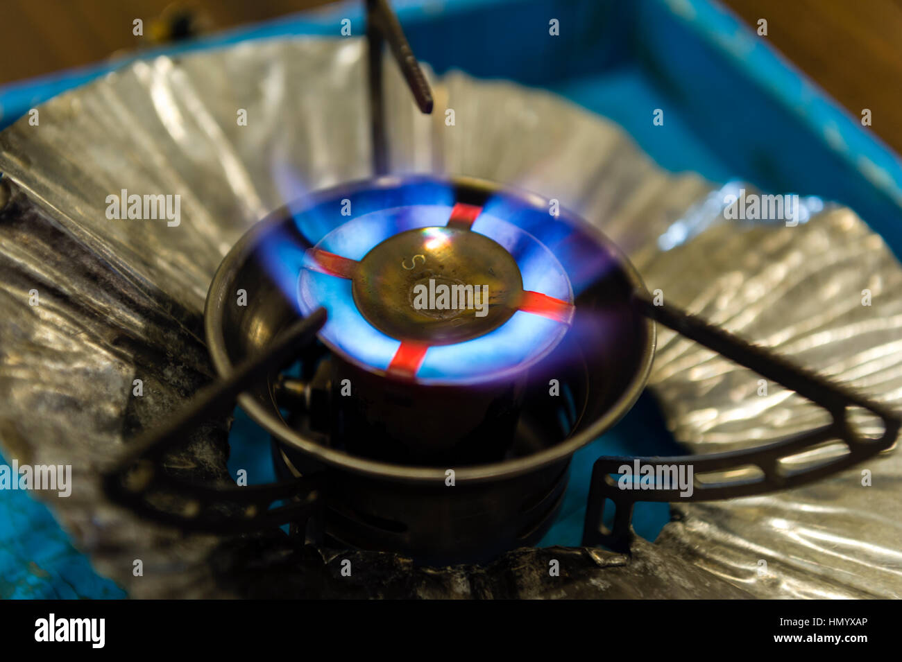A blue gas flame emerging from jets in an Antarctic camping cooker. - Stock Image