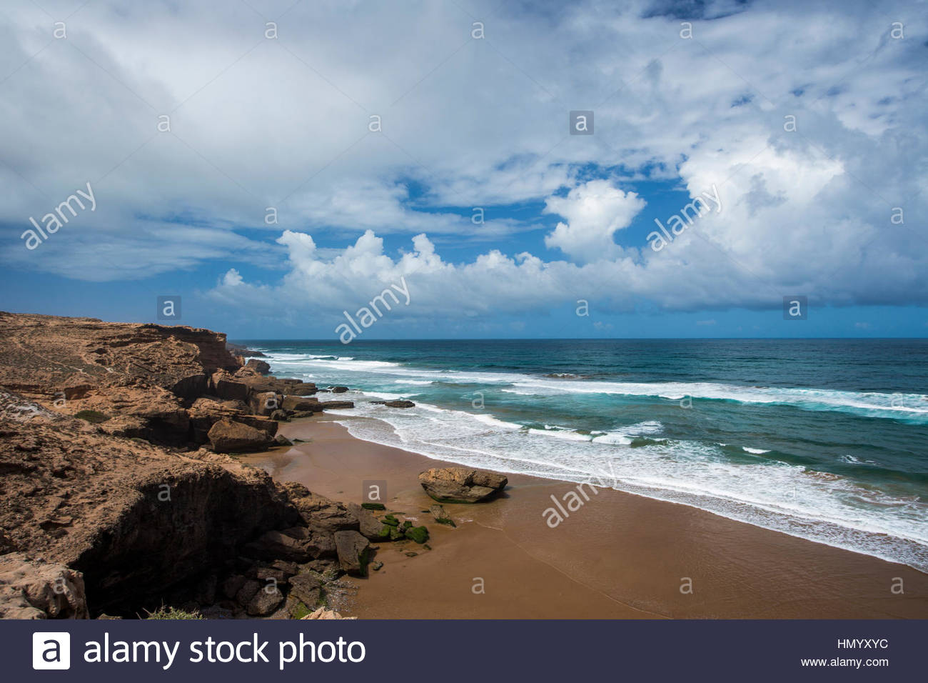 The rocky coastline and a flat beach north of Taghazout, Morocco on a sunny day. - Stock Image
