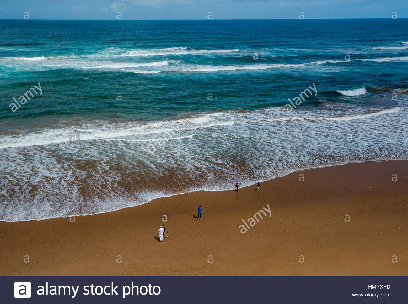 The coastline and a flat beach north of Taghazout, Morocco on a sunny day. - Stock Image