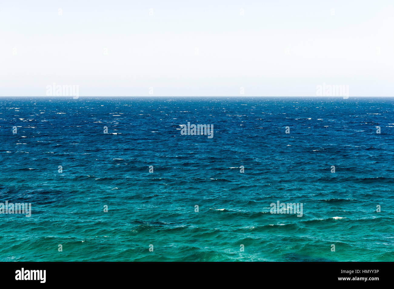 The wind-blown surface and horizon of a turquoise ocean. - Stock Image
