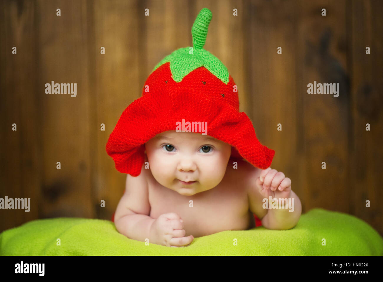 beautiful baby girl in a knitted hat strawberry stock photo