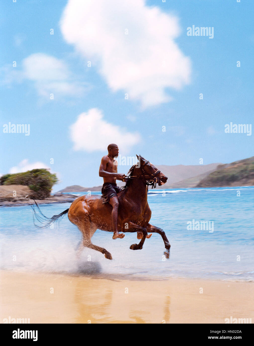 International Pony Club co-owner Alvin Phillipp rides a horse down Cas-En-Bas Beach. St. Lucia. - Stock Image