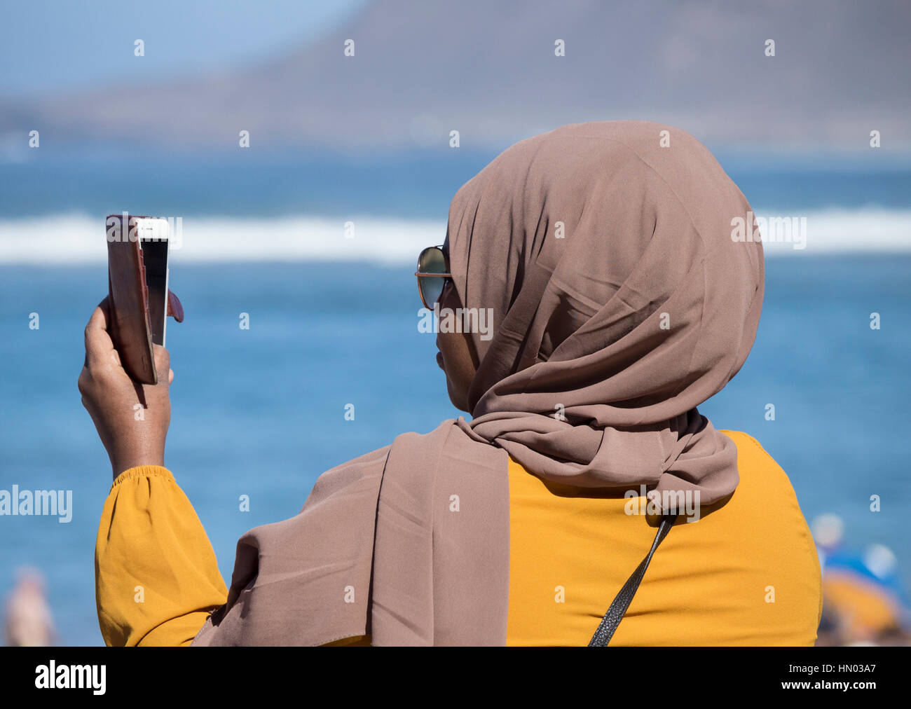 Woman wearing Hijab, headwear worn by Muslim women, taking selfie on beach in Spain - Stock Image