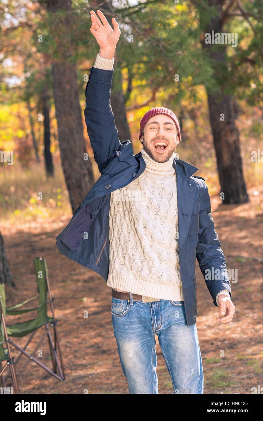 Smiling man waving hand - Stock Image