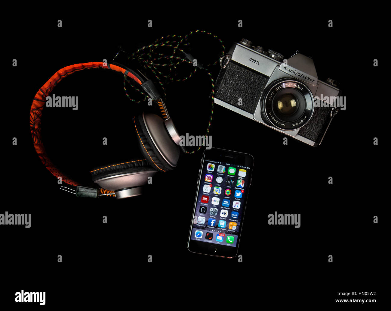 SWINDON, UK - FEBRUARY 7, 2017: Flat Lay with old SLR film camera, iPhone and headphones - Stock Image