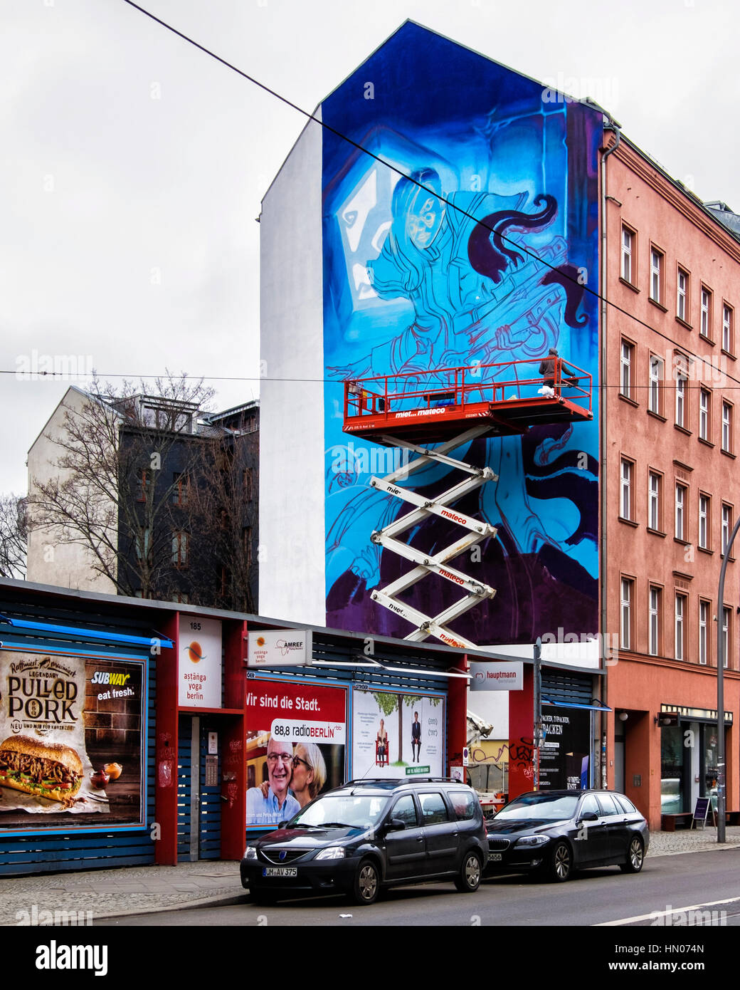 Berlin, Mitte. Commercial artist on scissor lift working on giant mural advertisement on building. - Stock Image