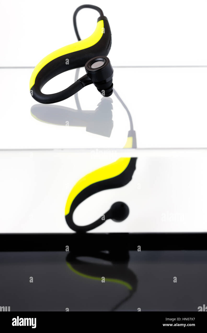 Yellow and black bluetooth earphones on an acrylic box with a black bottom - Stock Image