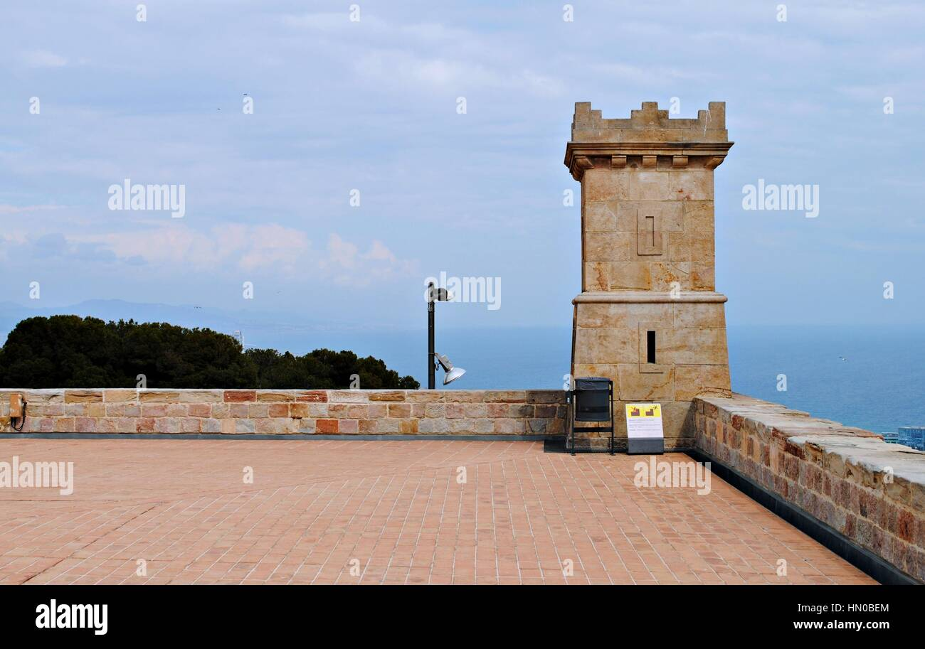 Stone Tower on the corner of the Castle of Montjuic, Barcelona, with blue sea background and cloudy blue sky - Stock Image
