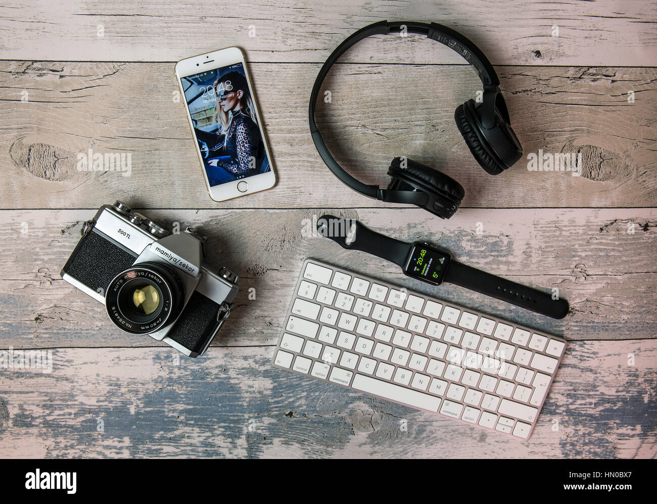 Flat Lay with old SLR film camera, iPhone, Apple watch, keyboard and headphones - Stock Image