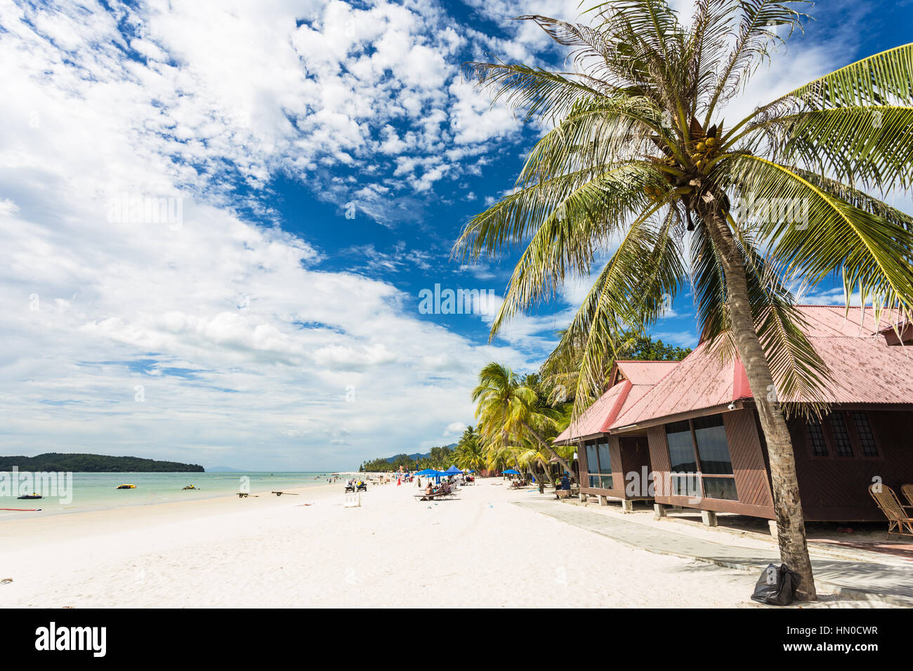 Palm tree and bungalow on Pantai Cenang, the most popular beach on the Langkawi island along the Andaman sea in - Stock Image
