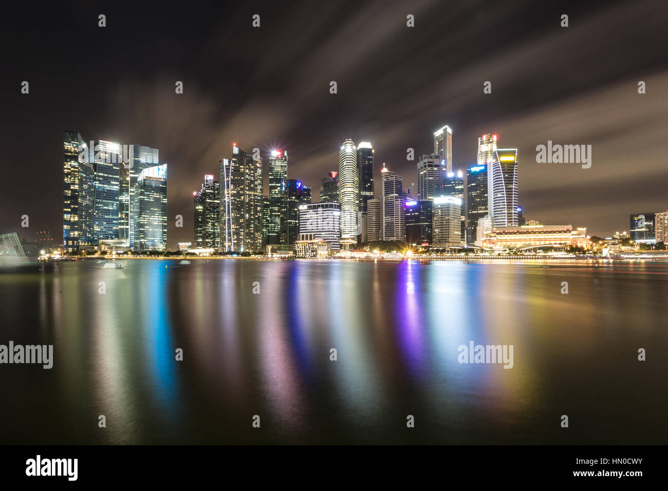 A reflection of the skyscrapers of Singapore business district skyline in the Marina bay from the waterfront promenade. - Stock Image