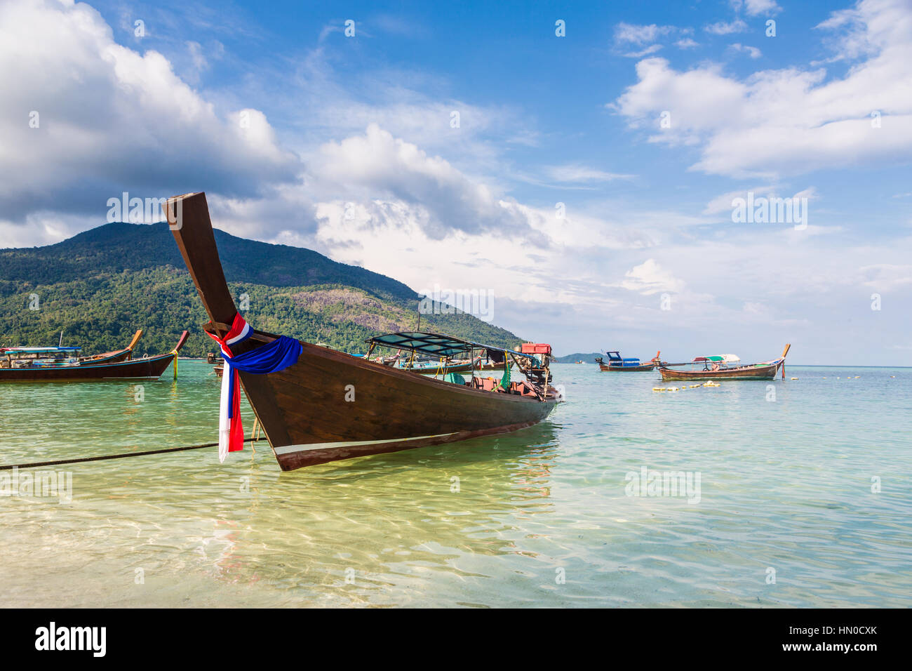 A low angle view of a traditional long tail on a beach in Koh Lipe island in the Andaman sea in south Thailand in - Stock Image