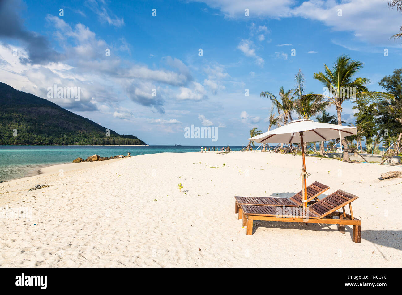 Idyllic white sand beach with long chairs and parasol in Koh Lipe island in south Thailand in the Andaman sea. - Stock Image