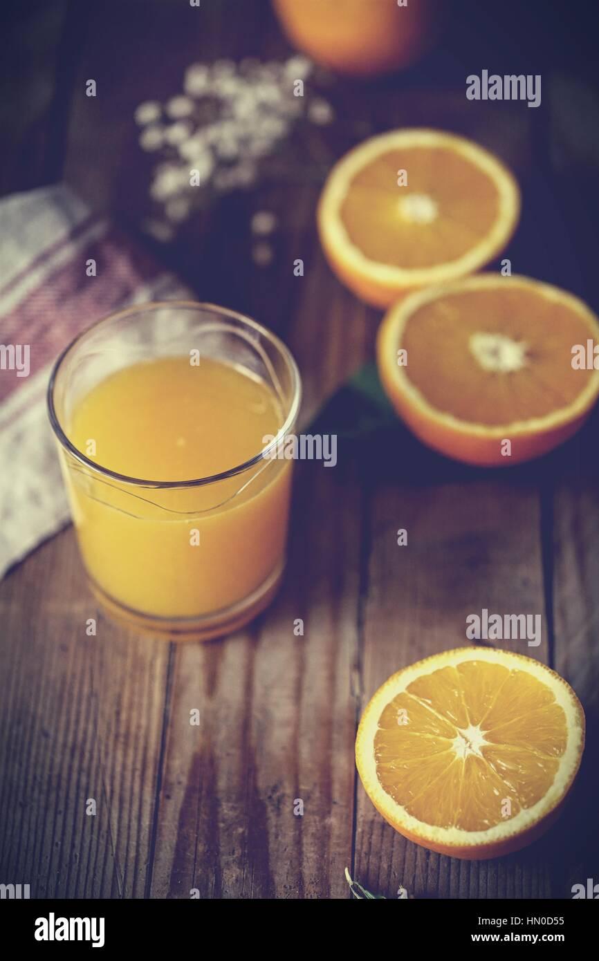 Halfed Ribera vanilla oranges and a glass of organic orange juice - Stock Image