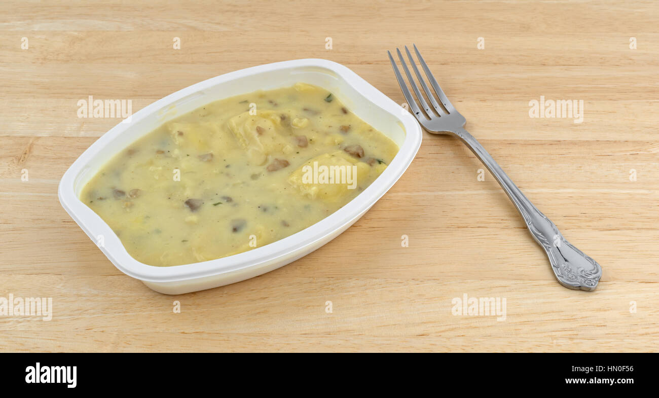 A fork to the side of a ravioli in a cheese and mushroom sauce TV dinner on a wood table top. - Stock Image