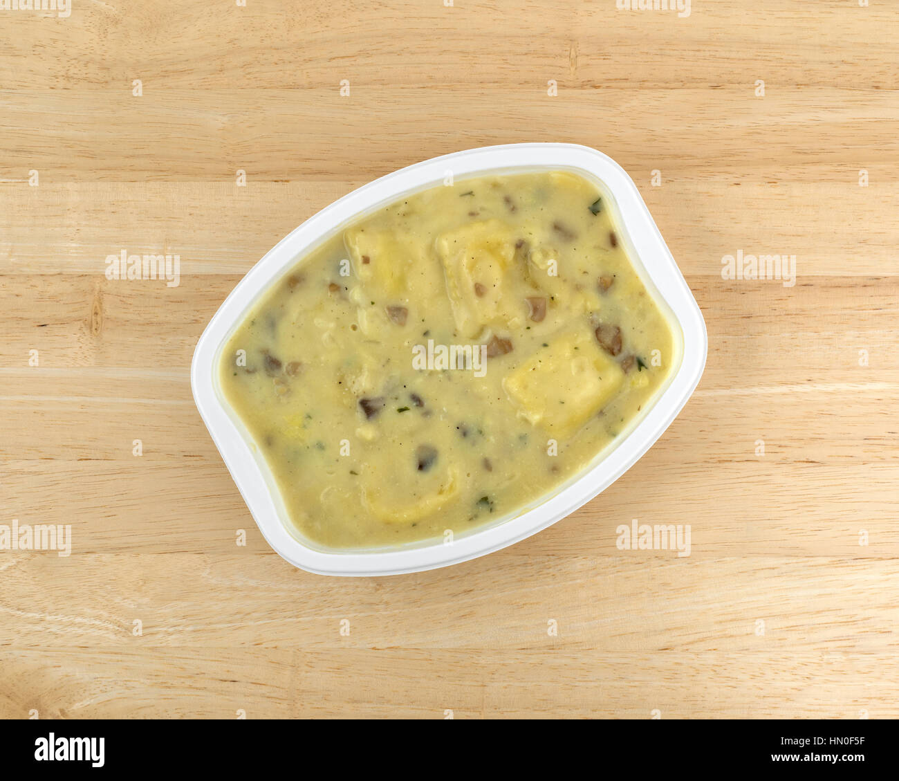 Top view of a ravioli in a cheese and mushroom sauce TV dinner on a wood table top. - Stock Image