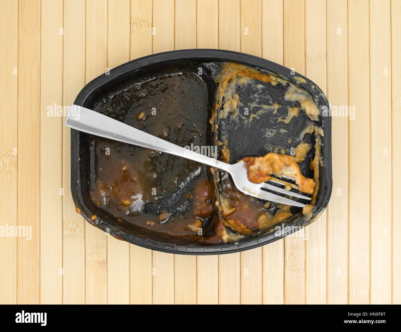 Top view of a finished barbecue and potato TV dinner with a fork in the tray atop a wood place mat. - Stock Image