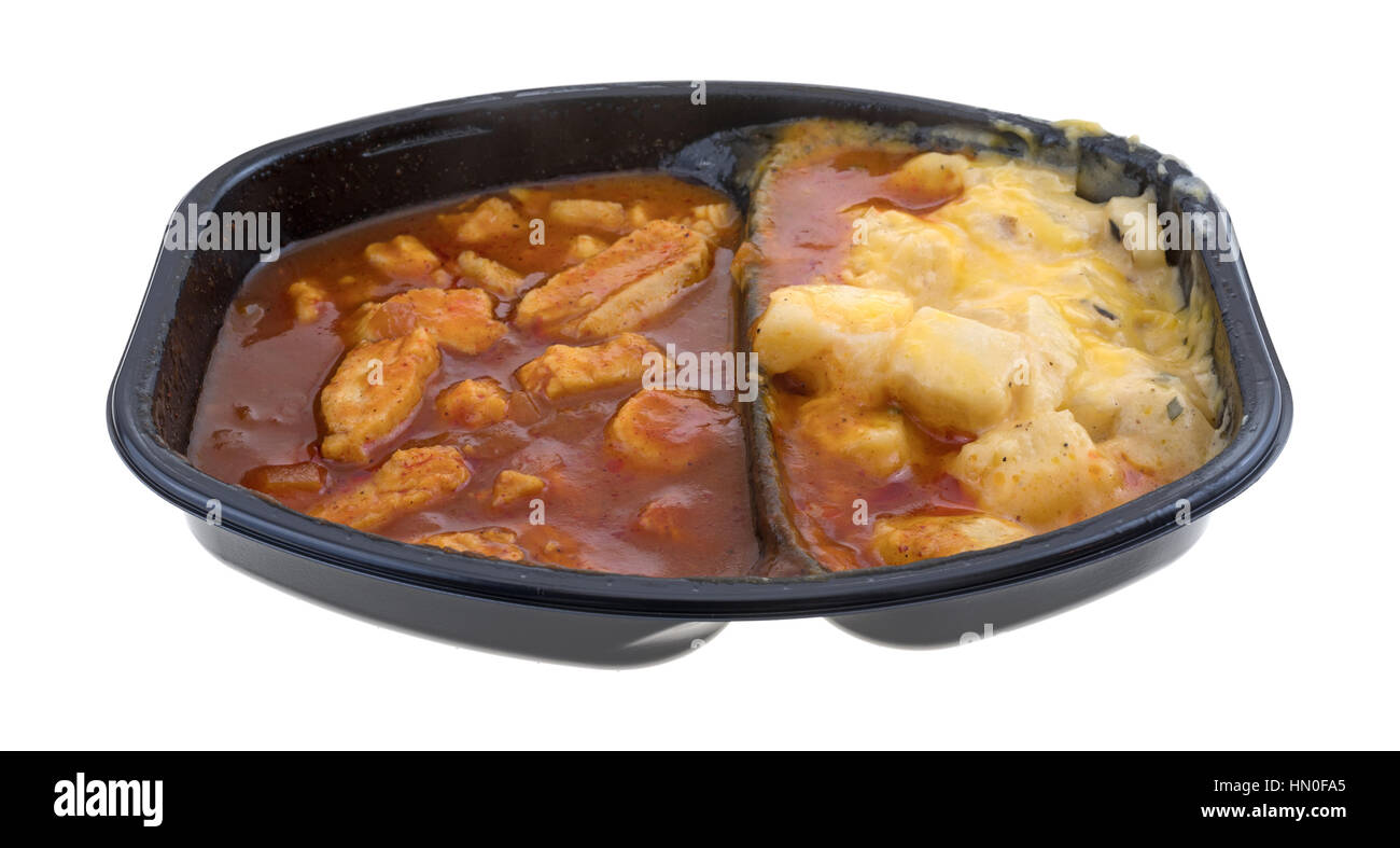 TV dinner with chunks of chicken in a thick barbecue sauce plus cheese covered potatoes isolated on a white background. - Stock Image