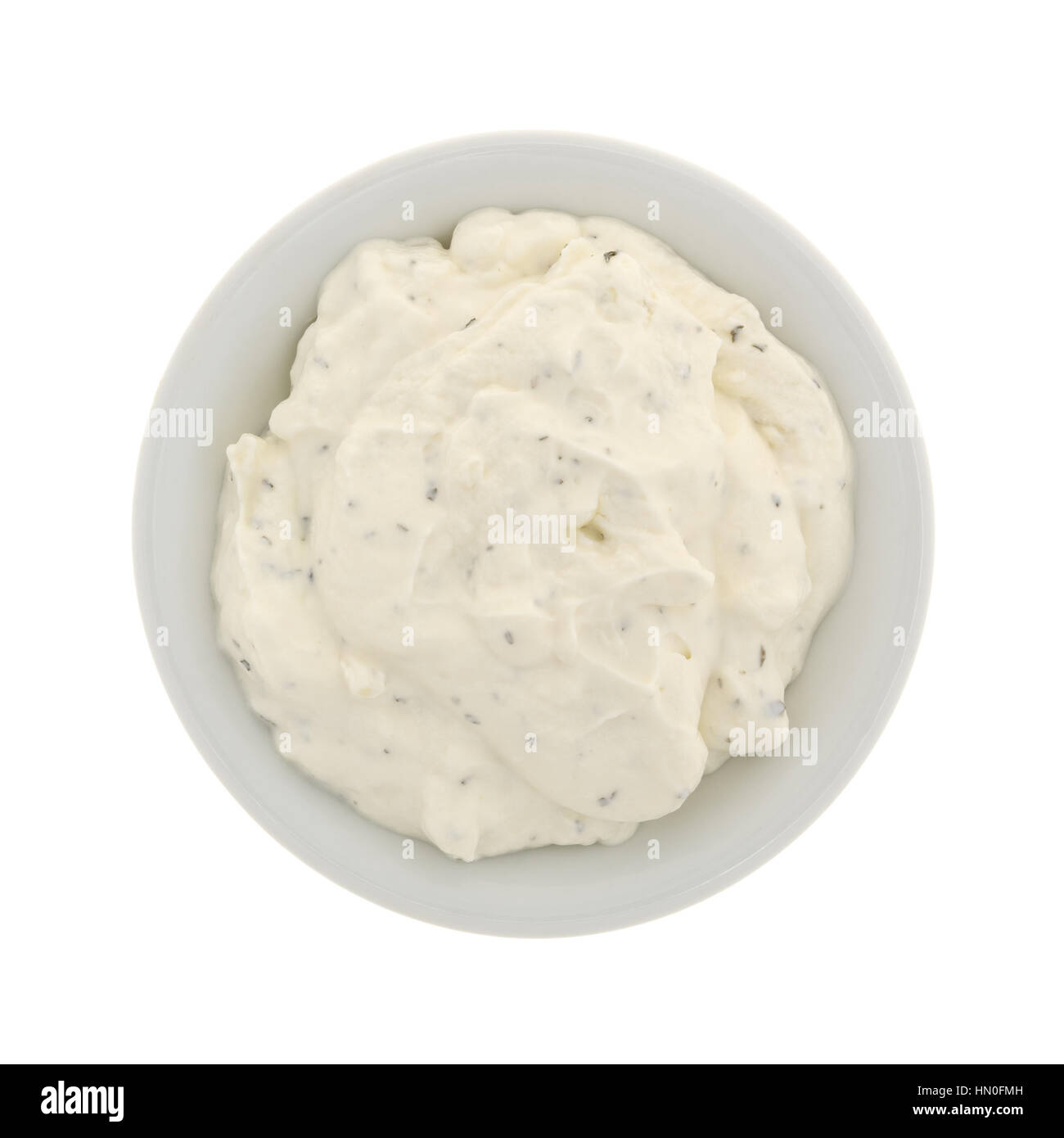 Top view of  a small bowl filled with fresh French onion dip isolated on a white background. - Stock Image