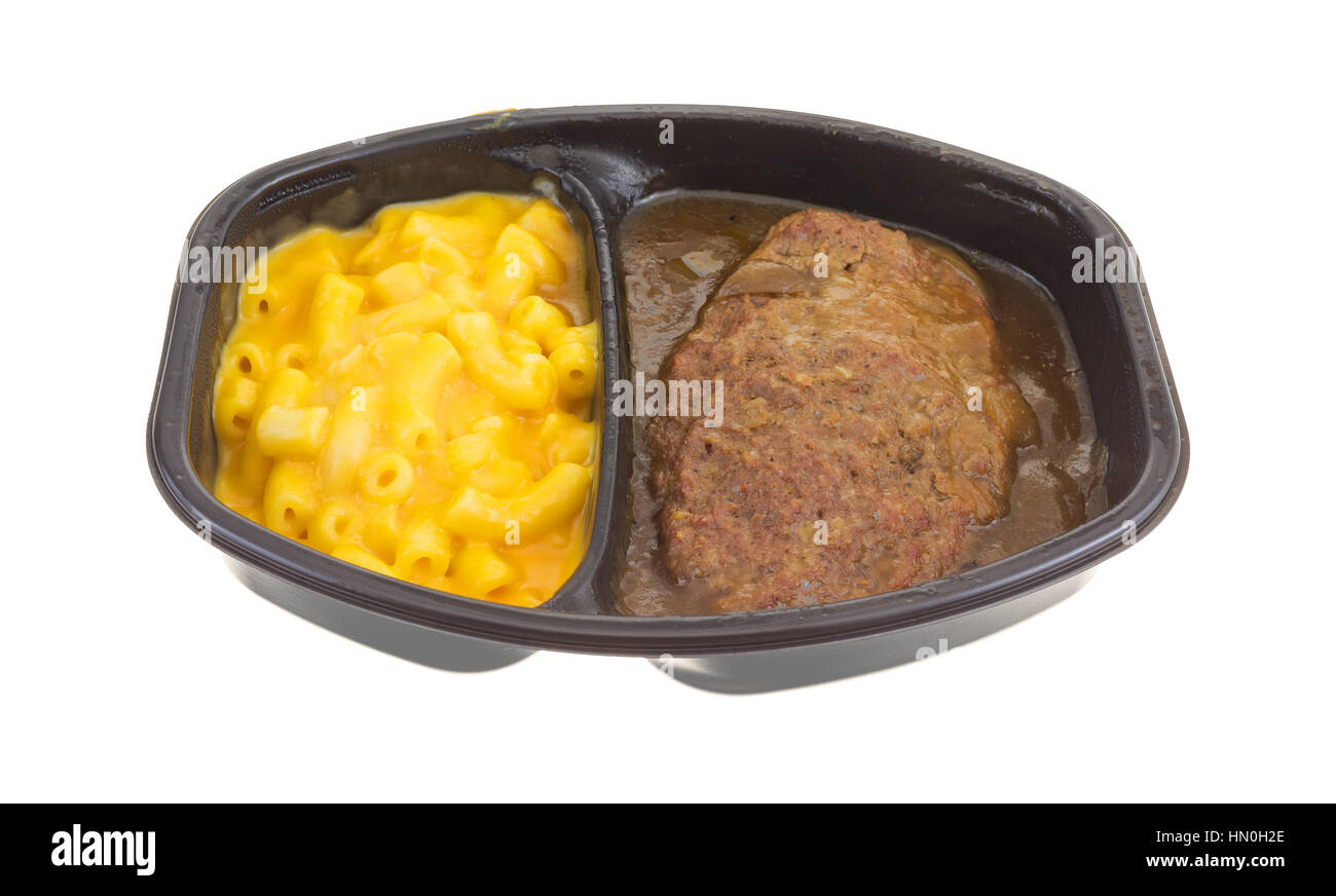 TV dinner meal of salisbury steak with gravy macaroni and cheese in a black tray isolated on a white background. - Stock Image