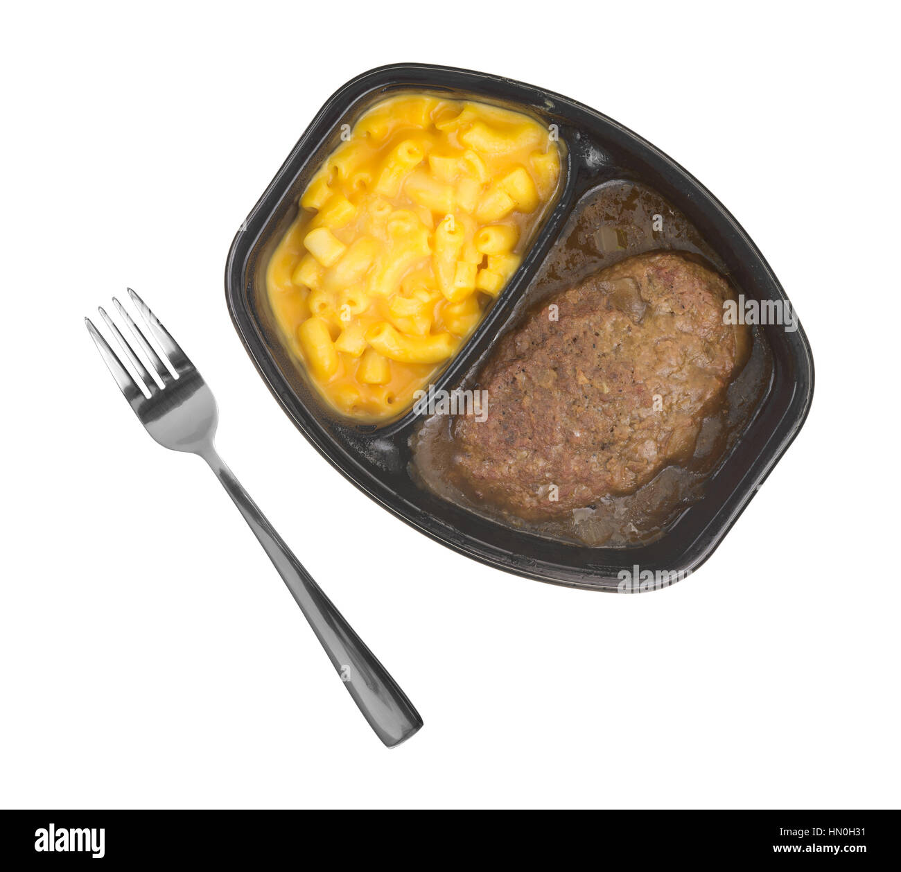 Top view of a TV dinner meal of salisbury steak with gravy macaroni and cheese in a black tray with a fork to the - Stock Image