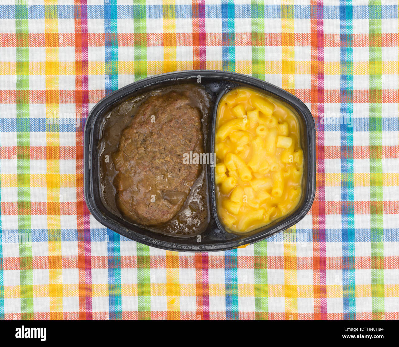 Top view of a TV dinner meal of salisbury steak with gravy macaroni and cheese in a black tray on a colorful place - Stock Image