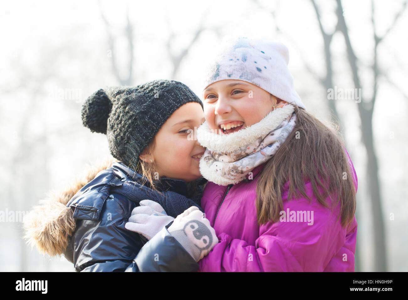 Two little girls with caps and scarves play - Stock Image