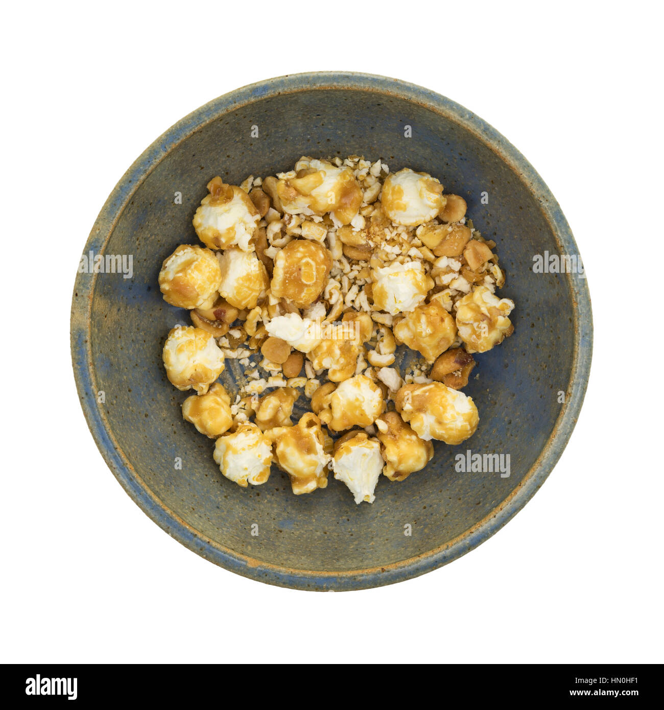 An old stoneware bowl with toffee caramel popcorn crumbs with nuts isolated on a white background. - Stock Image
