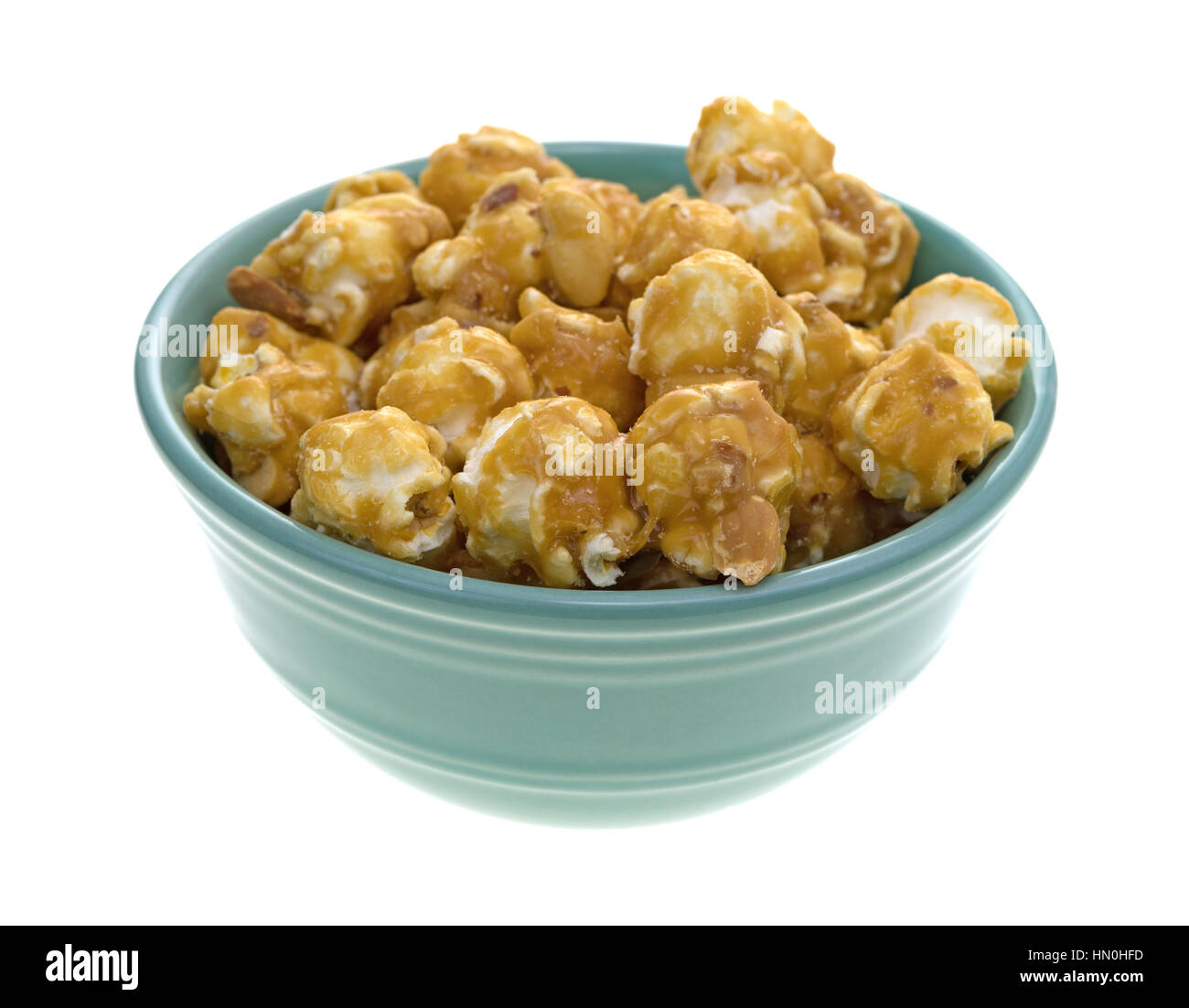 A green bowl filled with toffee caramel popcorn with nuts isolated on a white background. - Stock Image