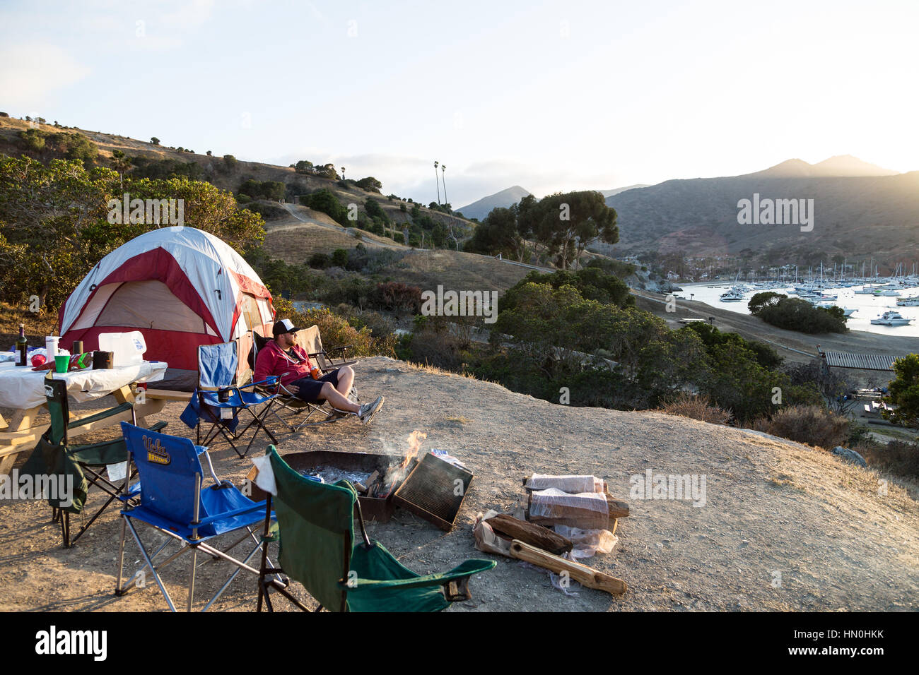 A man relaxes at camp as the sun sets over Two Harbors on Catalina Island. - Stock Image
