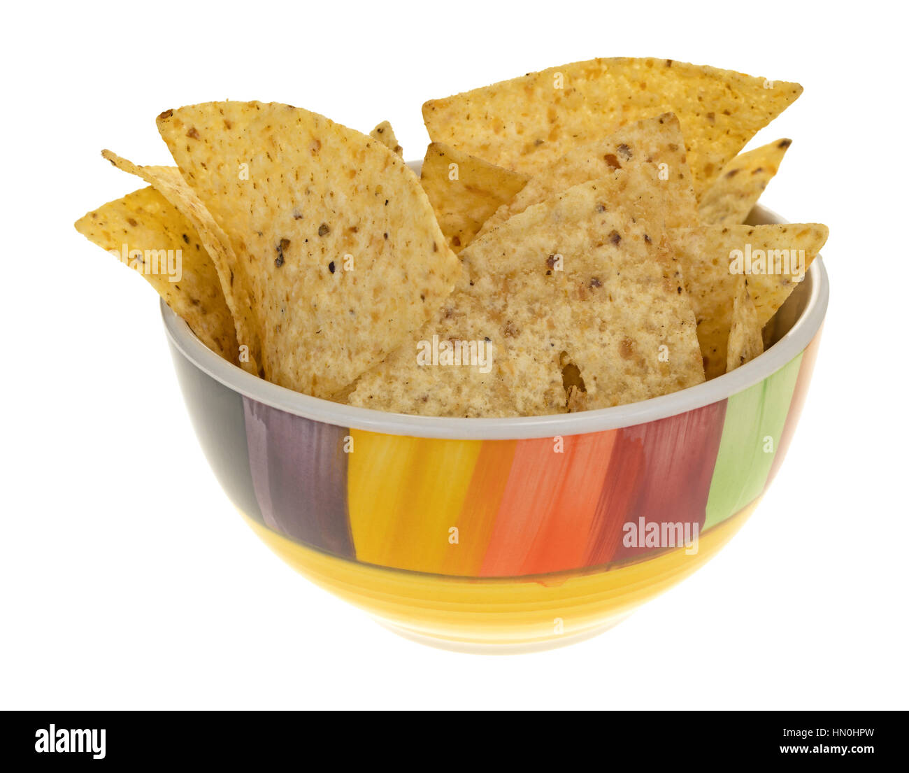 A colorful bowl filled with crispy tortilla chips isolated on a white background. - Stock Image